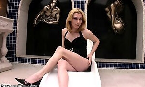 Leather wearing shemale performs a striptease and jerks off