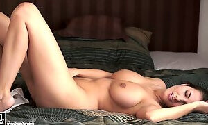 Beautiful brunette with nice, big tits lying down and rubbing her clit